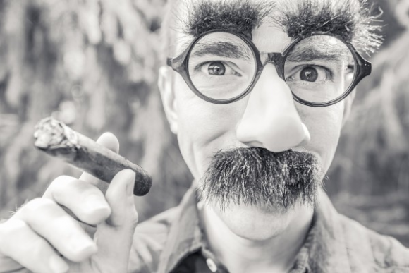 black-and-white-portrait-of-man-smoking-cigar-and-wearing-artificial-beard-and-eyebrows-1